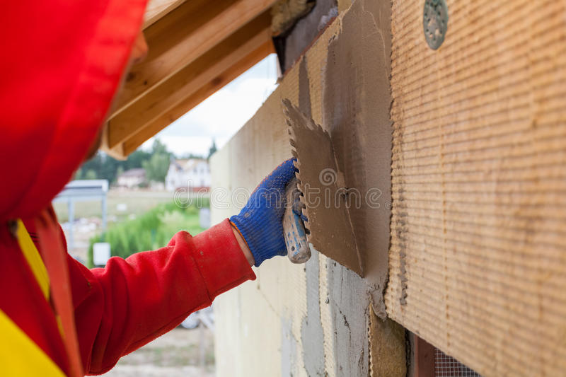 Worker plastering a facade of a new house on mineral rockwool panels. Process of insulation house for better energy efficiency stock image