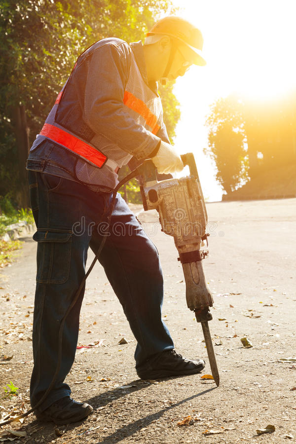 Worker with pneumatic hammer drill equipment. Ready to breaking asphalt at road royalty free stock photos