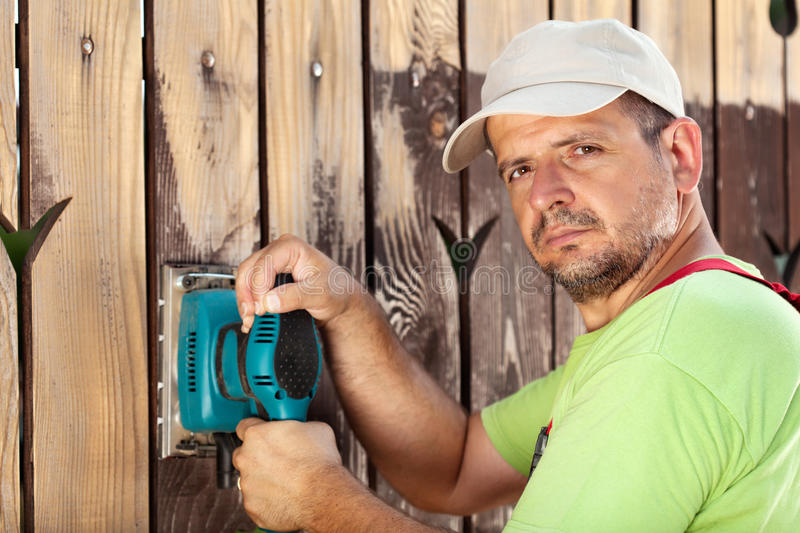 Worker polishing old wooden fence stock image