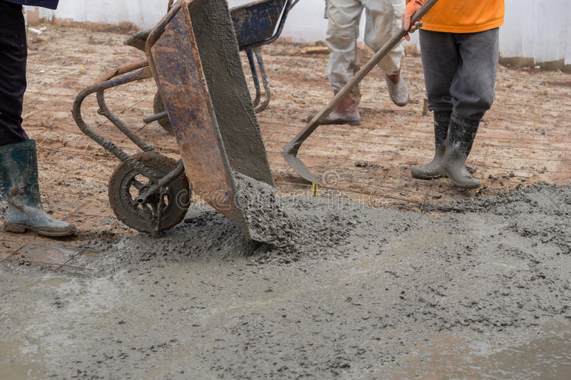 Worker pouring cement from cart to floor. At construction site stock photography