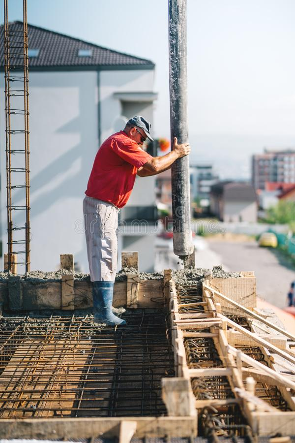 Worker pouring concrete details - concrete pouring during building of house royalty free stock photos