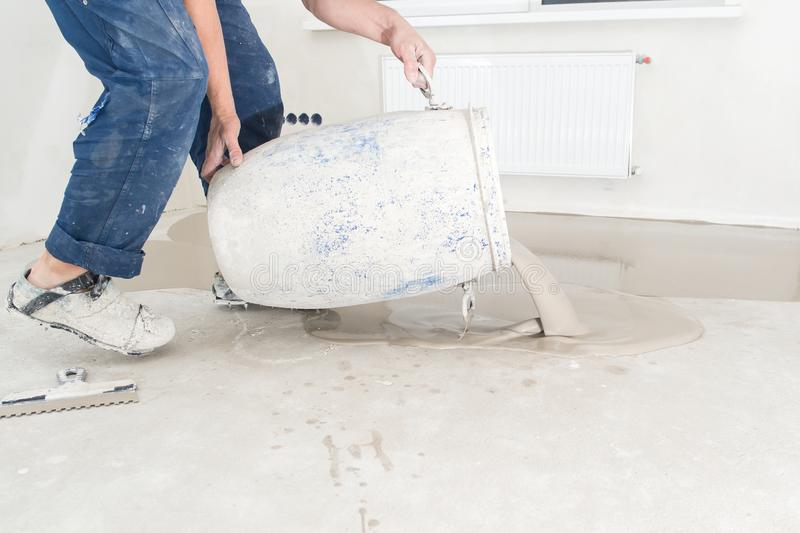 Worker pouring concrete on the floor in the room. Fill screed fl. Oor repair and furnish stock photos