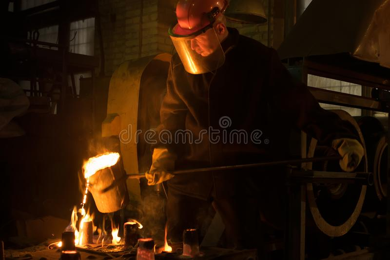 The worker pours melted metal from the ladle into the mold royalty free stock photography