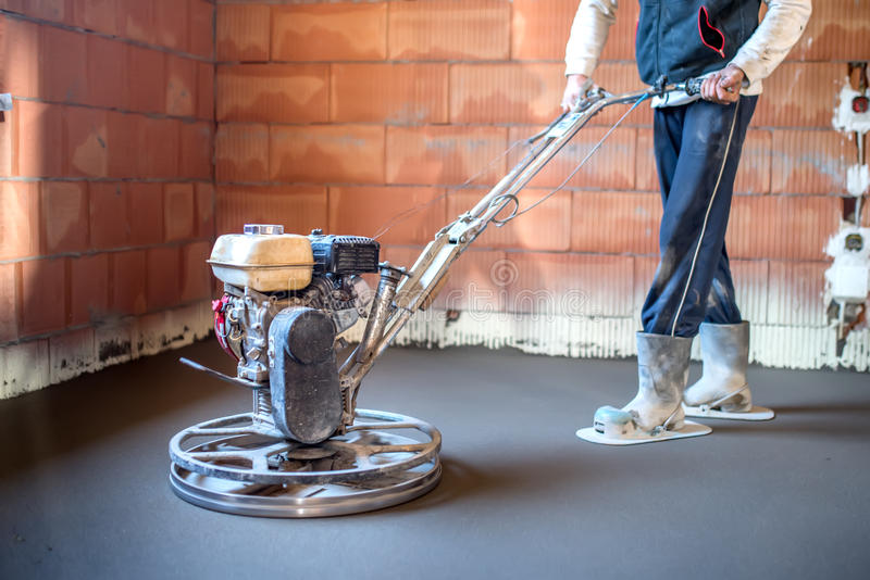 Worker with power trowel tool finishing concrete floor, smooth concrete surface at house construction. Worker with power trowel tool finishing concrete floor royalty free stock photography