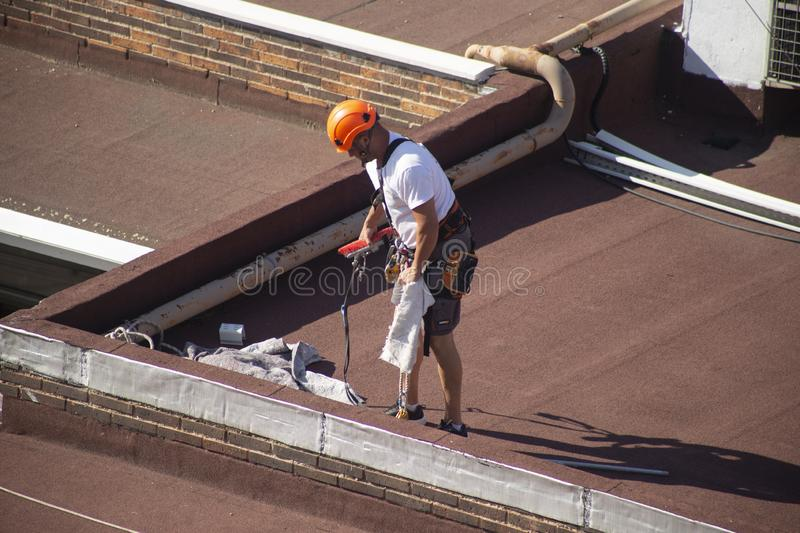 Madrid, Spain - September, 04, 2019: work at height. Worker with harness for dangerous work. A worker prepares with the helmet and harness to work at height from royalty free stock image