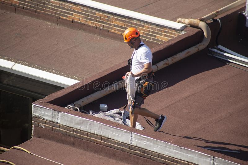 Madrid, Spain - September, 04, 2019: work at height. Worker with harness for dangerous work. A worker prepares with the helmet and harness to work at height from stock photography