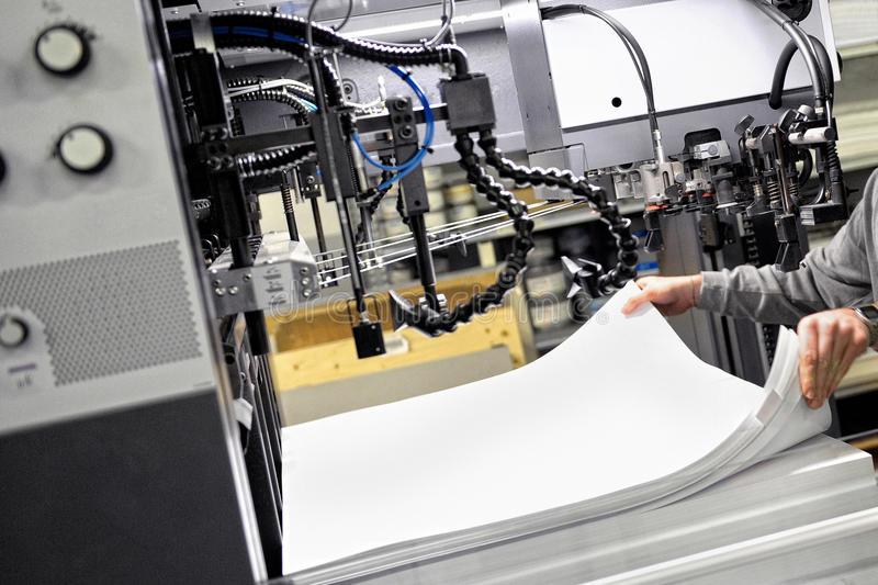 Worker Preparing Papers for Print at the Machine royalty free stock photography