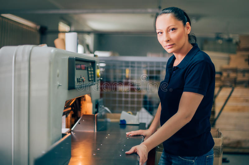 Worker in printing centar uses paper guillotine machine knife royalty free stock photography
