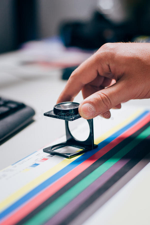 Worker in printing and press centar uses a magnifying glass stock photography
