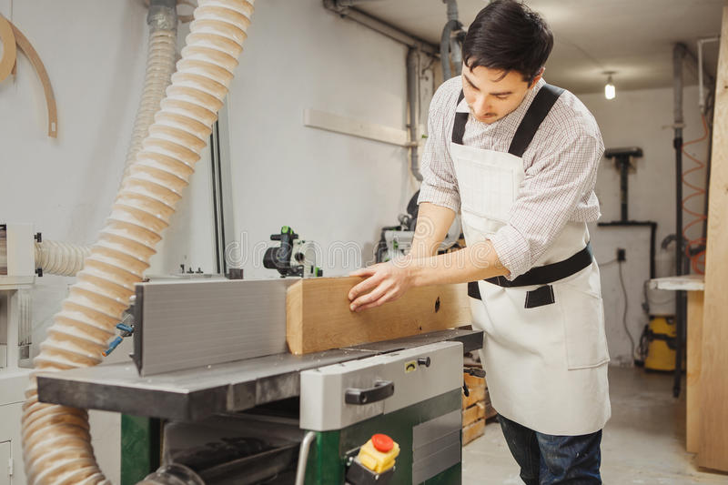 Worker processes board on woodworking machine. Young man dressed in protective overalls, checkered shirt and jeans. Room equipped with hood royalty free stock photo