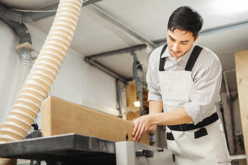 Worker processes board on woodworking machine. Young man dressed in protective overalls, checkered shirt and jeans. Room equipped with hood royalty free stock photography