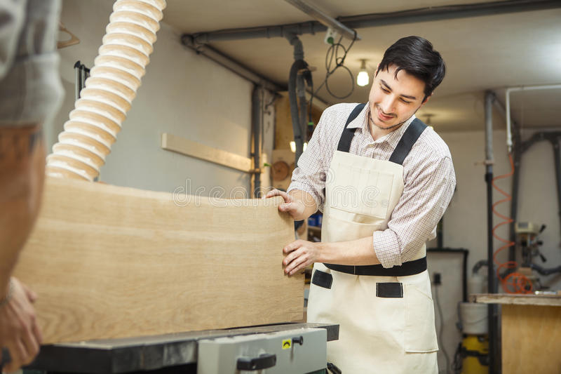 Worker processes board on woodworking machine. Young man dressed in protective overalls, checkered shirt and jeans. Room equipped with hood royalty free stock image