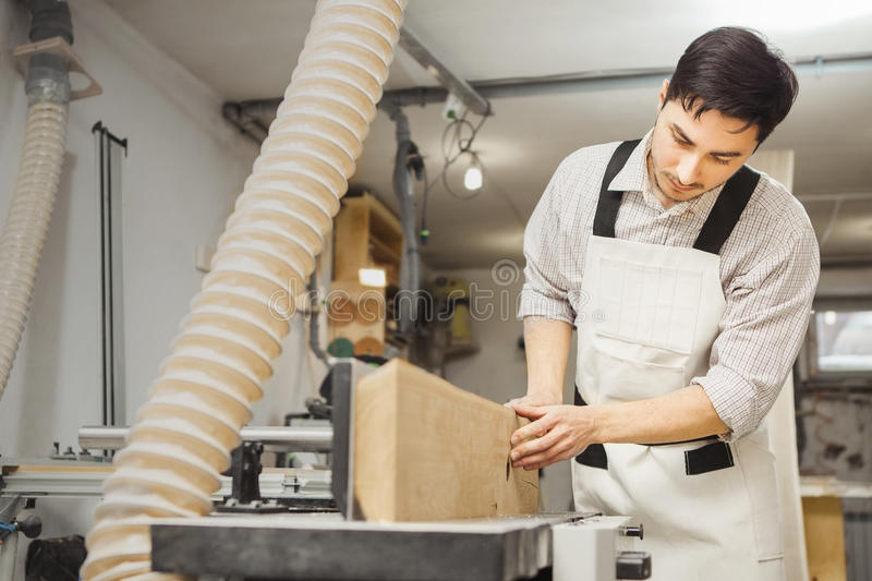 Worker processes board on woodworking machine. Young man dressed in protective overalls, checkered shirt and jeans. Room equipped with hood royalty free stock images