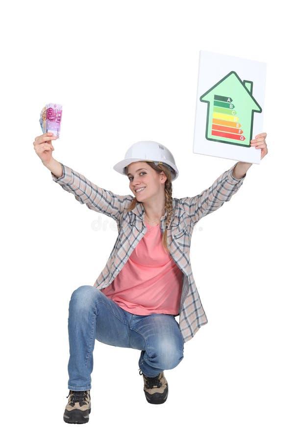 Worker promoting energy savings. A female construction worker promoting energy savings stock image