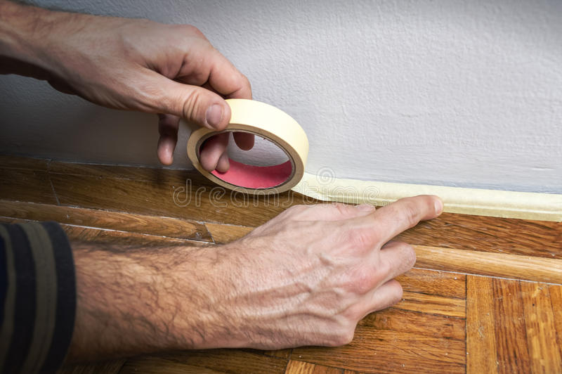 Worker protecting batten moulding with masking tape before paint. Ing at home improvement work stock photo
