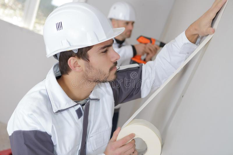 Worker protecting wall with masking tape before painting stock photo