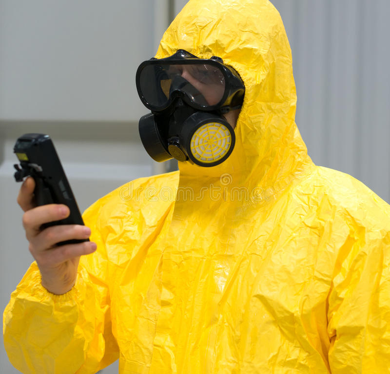 Worker in protective chemical suit. Worker in protective chemical suit checking radiation with geiger counter royalty free stock images