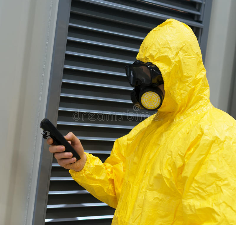 Worker in protective chemical suit. Worker in protective chemical suit checking radiation with geiger counter royalty free stock photos