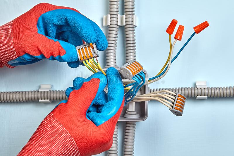 Worker in protective gloves installs junction box. Electrician is mounting electrical junction box with twist splice wire connectors and pluggable connection royalty free stock image