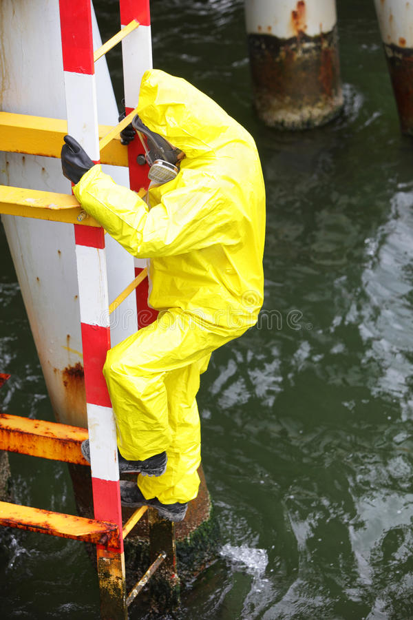 Worker in protective suit climbing ladder over the sea. Worker in protective suit and mask, climbing ladder over the sea stock photography