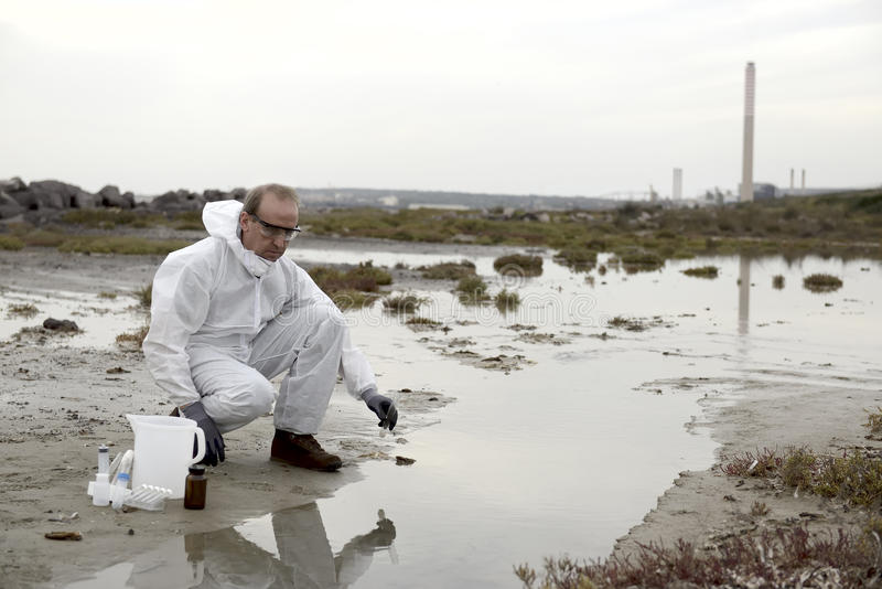 Worker in a protective suit examining pollution royalty free stock photography