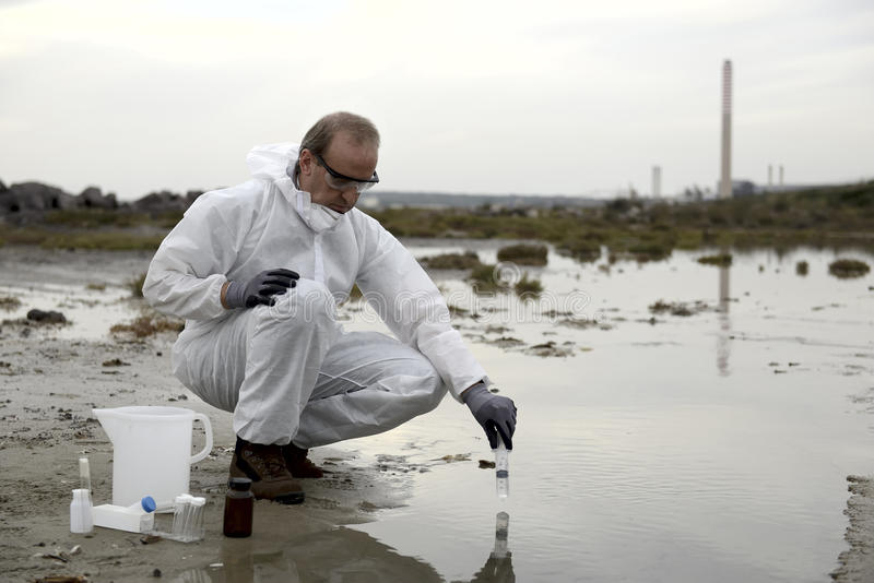 Worker in a protective suit examining pollution. In the water at the industry royalty free stock photos