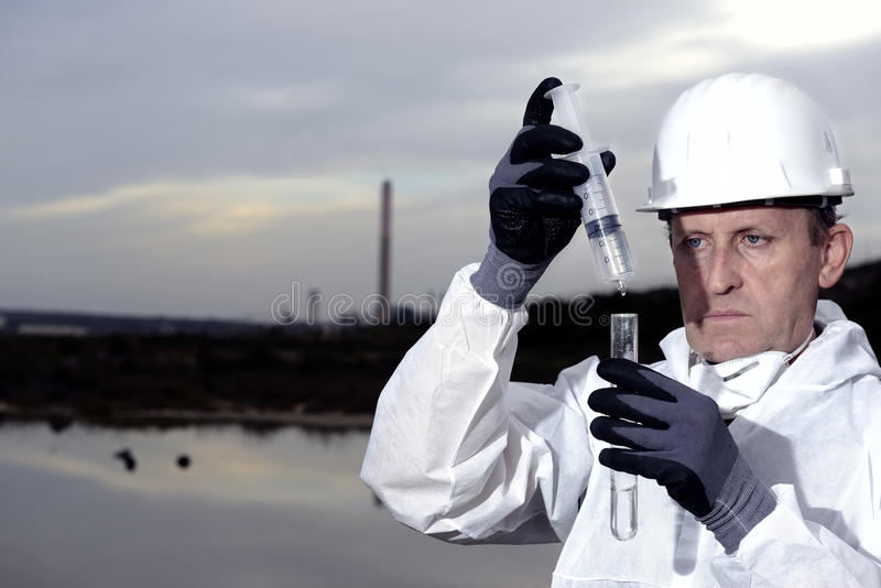 Worker in a protective suit examining pollution. Worker in a protective suit examining pollution in the water at the industry royalty free stock images