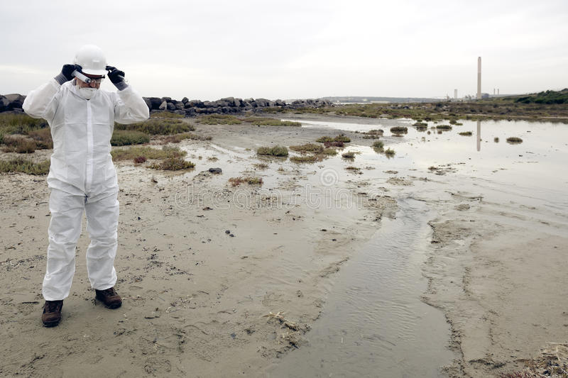 Worker in a protective suit examining pollution. In the water at the industry. Gray sky. Blanck area royalty free stock photography