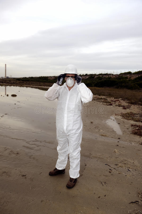 Worker in a protective suit examining pollution stock photography