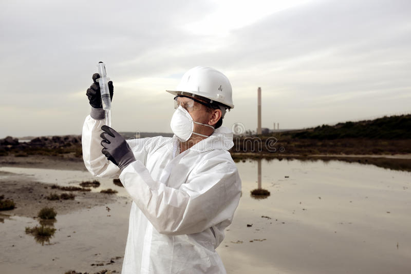 Worker in a protective suit examining pollution. In the water at the industry. Gray sky. Blank area stock photos