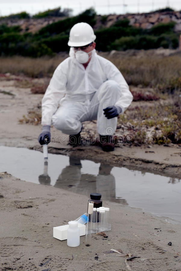 Worker in a protective suit examining pollution stock image