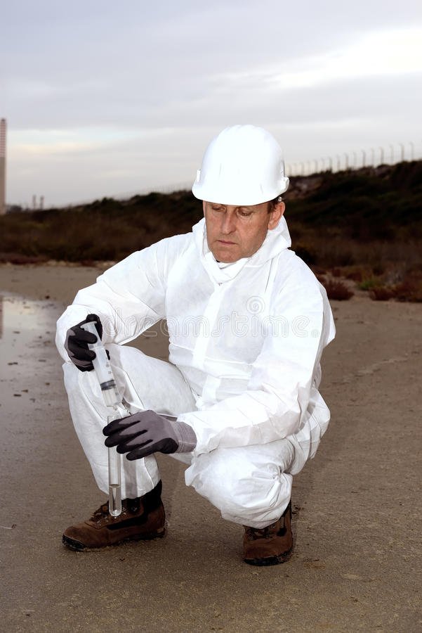 Worker in a protective suit examining pollution. royalty free stock images