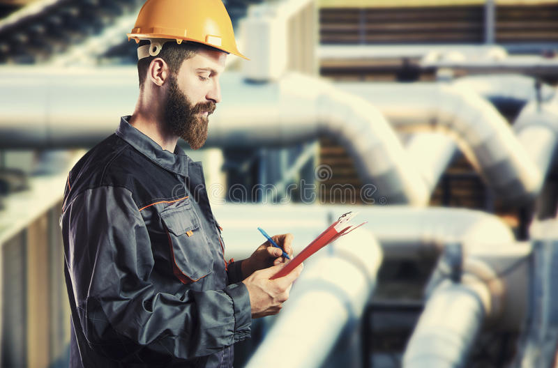 Worker in protective uniform, protective helmet, and clipboard royalty free stock image