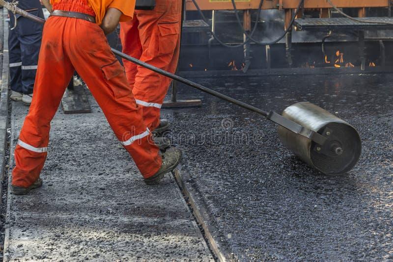 Worker pushing hand roller for mastic asphalt paving stock photos