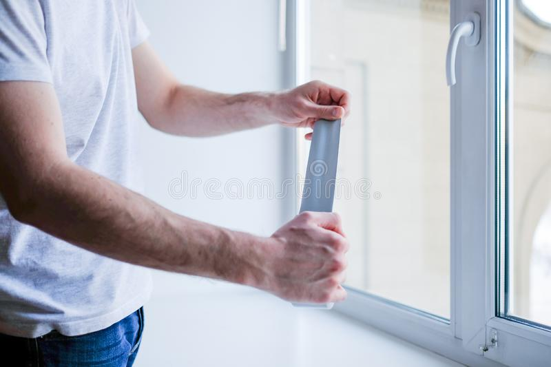 Worker putting sealing tape on window in house royalty free stock image
