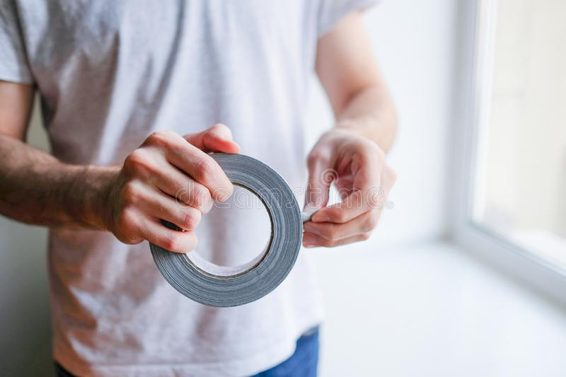 Worker putting sealing tape on window in house royalty free stock images