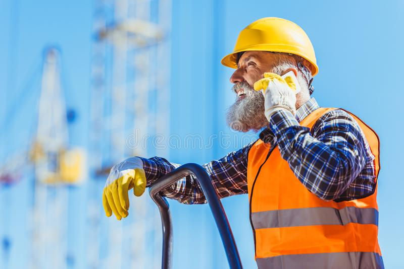 Worker in reflective vest and hardhat talking on smartphone at construction site with cranes stock images