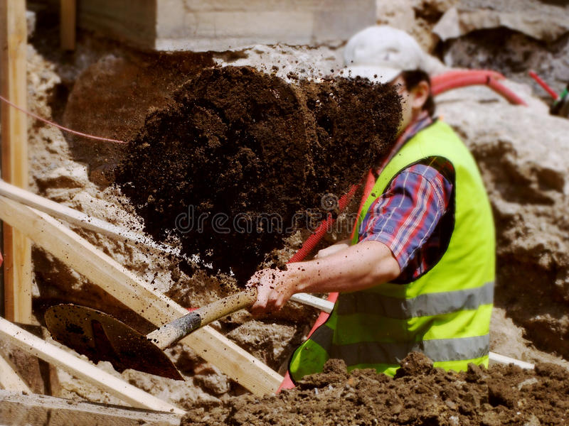 Worker with reflective vest shoveling clay royalty free stock images
