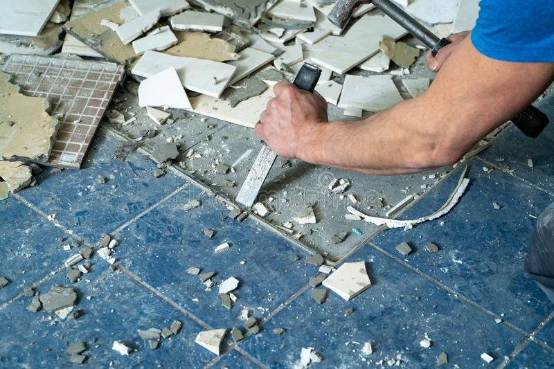 Worker remove, demolish old tiles in a bathroom with hammer and chisel stock photography