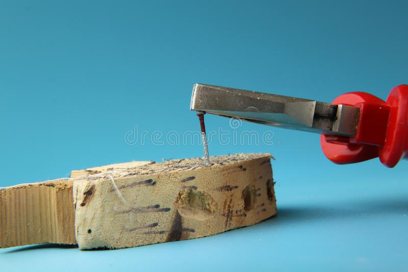 A worker remove rust nail with helper combination pliers. Manual hard work royalty free stock photos