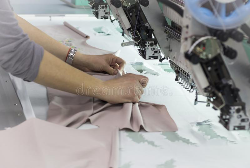 The worker removes the finished embroidery from the embroidery frame on the embroidery machine.  stock photo