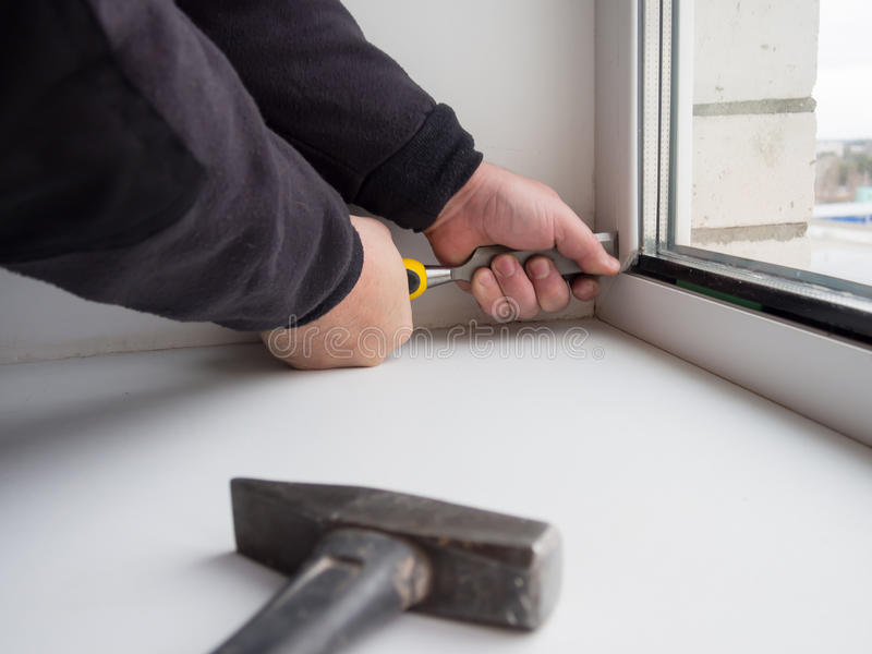 Worker removes the lock insulating glass of a plastic window stock photos