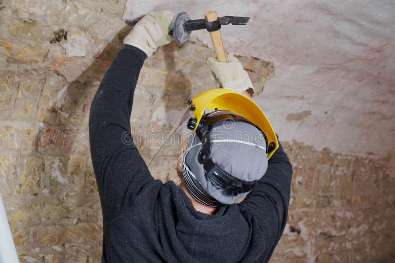 Worker removing plaster from the wall with tools royalty free stock photos