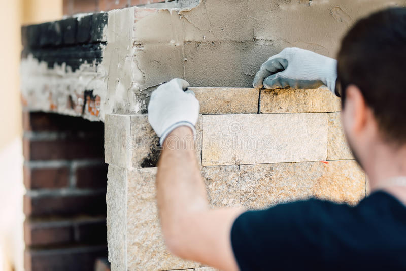 worker renovating exterior walls and installing stone with mortar stock photos