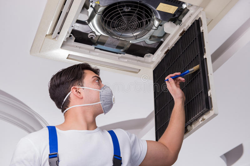 The worker repairing ceiling air conditioning unit. Worker repairing ceiling air conditioning unit stock photo