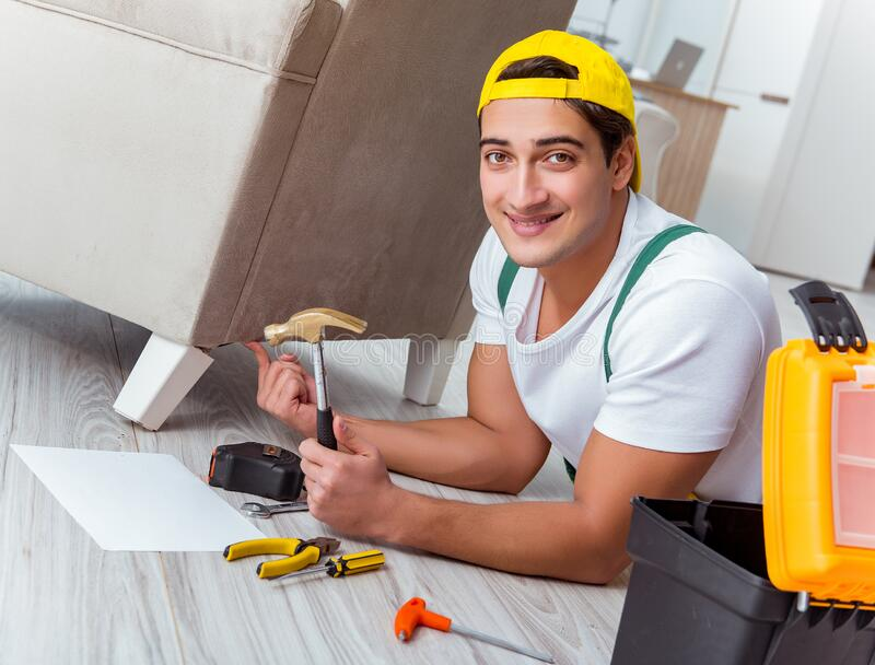 Worker repairing furniture at home stock photo
