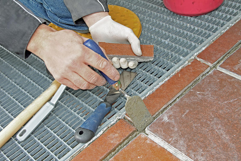 Worker repairing and grouting patio. Outdoors royalty free stock photo