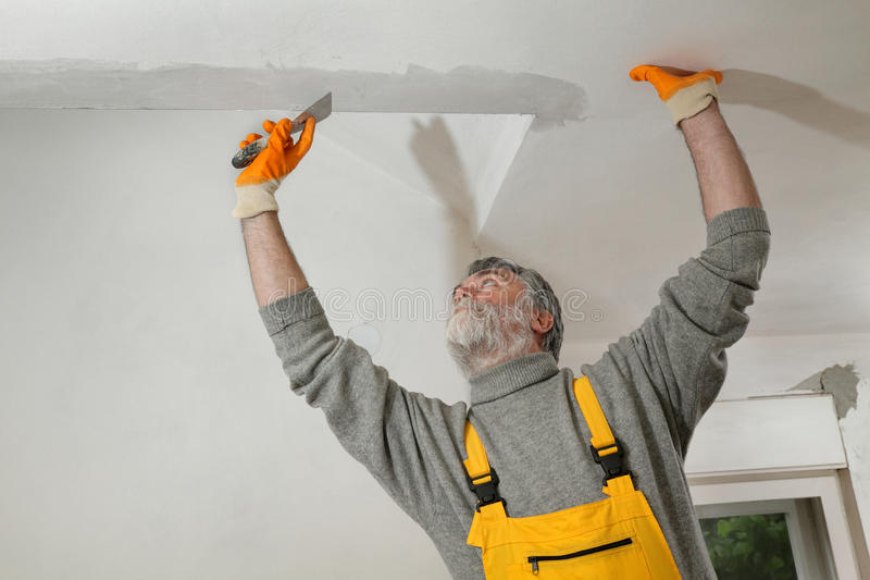 Worker repairing plaster at ceiling. Worker spreading plaster to wall, corner protecting batten install, repairing works stock photos