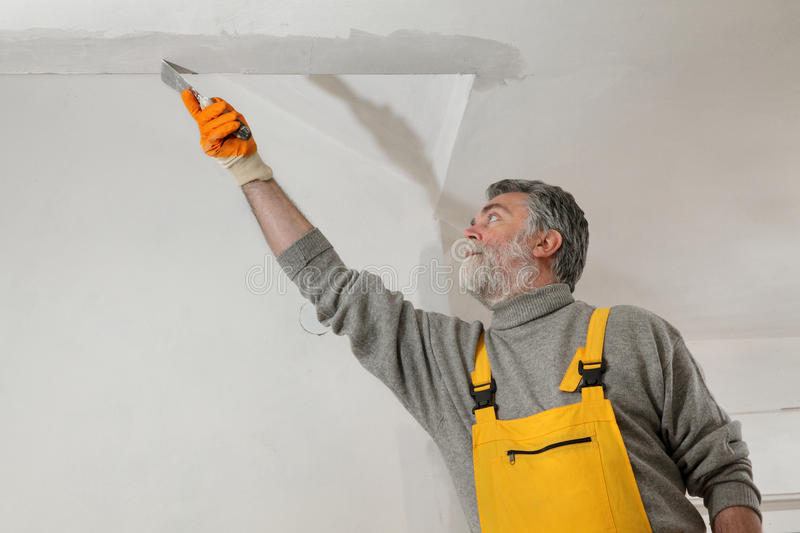 Worker repairing plaster at ceiling. Worker spreading plaster to wall, corner protecting batten install, repairing works royalty free stock photo