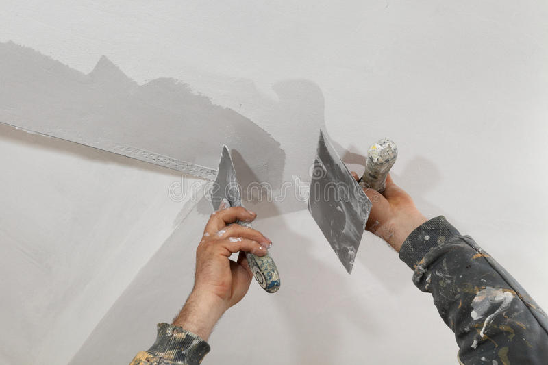 Worker repairing plaster at ceiling. Worker spreading plaster to wall, corner protecting batten install, repairing works stock photography
